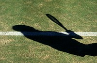 Shadow of a tennis player on a grass court