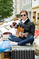 Young man plays guitar sitting on an old fridge in front of a pile of garbage, in Cologne, North Rhine-Westphalia, Germany, Europe