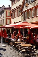 Bar café restaurant terraces in the historic centre in summer, guests and red sunshades on the Marktplatz Square, Heidelberg, Neckar Valley, Baden-Wue...