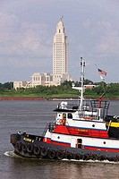 Tugboat crossing by a government building, Louisiana State Capitol, Baton Rouge, Louisiana, USA