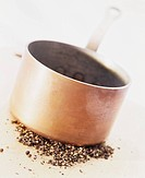 Peppercorns being crushed by a copper pan