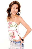 A beautiful young asian woman in a flowery top and denim skirt