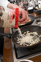 Sweating rice and onions in a frying pan for risotto