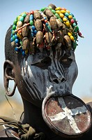 White painted woman from the Mursi tribe with a plate lip and colourful beads on her head, near Jinka, Ethiopia, Africa