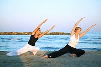 two women doing yoga at the beach