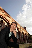 Portrait of a young man wearing a suit, sitting in front of an industrial building made of red bricks looking into the distance, thinking
