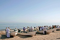 fishermen at their boats on the beach of Barka, Oman