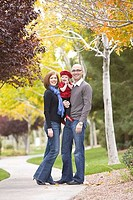 Family smiling in a park