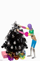 A colorful female manikin decorates a black Christmas tree  She has a heart decoration on her arm
