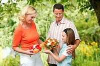 family, girl giving present and flowers to mother
