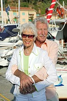senior citizen couple on holiday strolling at harbour area