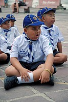 schoolboys sitting cross_legged, Wat Phrachetuphon school, Thailand, Bangkok