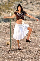 beautiful Latina woman in a white skirt and brown top, standing in the desert with one foot up on a barbed wire fence