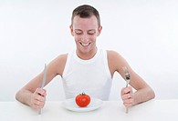 young man with tomato at plate