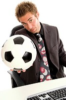 business man in office holding football towards the camera