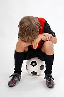 boy sitting on a football