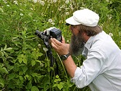 nature photographer taking close_up photos of an insect, Denmark