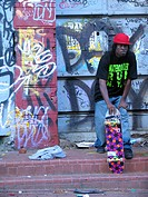 Skateboard_rider in front of wall with graffiti under the Manhattan_Bridge, USA, Manhattan, New York