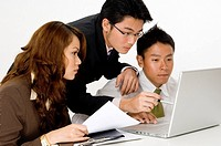 Three asian business people looking at a laptop computer