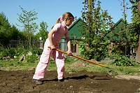 child burrowing the soil in the garden of a primary school to make a flower bed