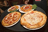 Cheese and peperoni pizzas with two plates of breaded fried cheese and marinara sauce on a waiters tray