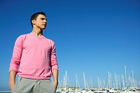 Handsome young man on summer in harbor, blue sky