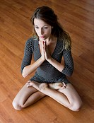 young woman practicing yoga on parquet floor