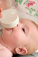 Baby blond little girl feeding drinking milk in a bottle