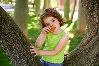 Beautiful little girl eating biscuit over the green park tree