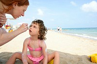 Daughter and mother on the beach sun screen protection moisture cream