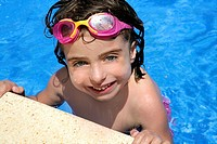 beautiful little girl smiling in blue water with pink goggles