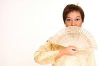 A young Malay woman wearing a traditional outfit holds a wooden fan to her face