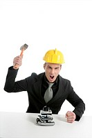 Angry businessman, hammer against telephones, yellow helmet