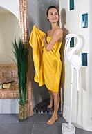 young woman in yellow towel standing her bathroom