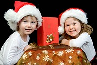 christmas kids with christmas gift in front of black background