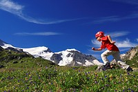 boy wearing swiss wear, running through a flower meadow at the Gwaechtenhorn, Switzerland, Berne, Bernese Oberland, Steingletscher
