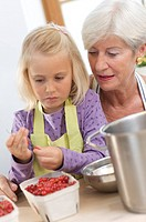 girl with grandmother cooking jam