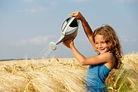 Girl watering a wheat field