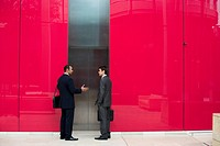 Two Businessmen Talking by Elevator
