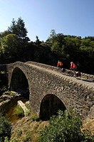 Bicyclists on an old Roman bridge near Lamastre, Ardèche, Rhones-Alpes, France, Europe