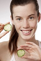 Teenage girl, woman, 17 years-old, holding cucumber slices, smiling