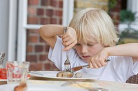 boy eating with knife and fork