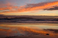 Sunrise, spectacular sunrise over the ocean with clouds blazing in all hues of yellow and red and mirroring themselves on the wet beach, New Zealand, ...