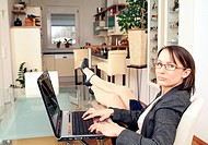 young business woman using laptop at home, her legs on the table
