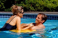 romantic couple enjoy each others company in the swimming pool, USA
