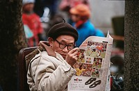 man reading newspaper, China, Chengdu
