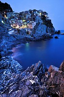 Village of Manarola nestled atop steep coastline at dusk, Liguria, Cinque Terre, Italy, Europe