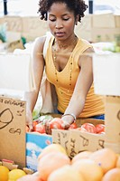 African woman picking vegetables in market
