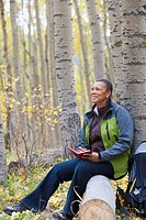 Black woman writing in diary in forest
