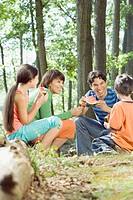 Family eating watermelon in forest